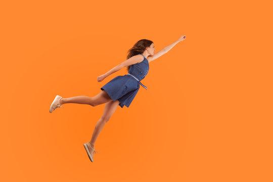 Superhero. Full length of confident motivated brunette woman in denim dress flying in air like superman and feeling superpower, striving up for success, reaching goal. studio shot orange background