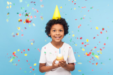 Happy cheerful cute little boy with funny party cone on head holding cupcake and smiling while confetti falling around, his look expressing pure joy and happiness. indoor studio shot blue background