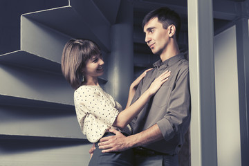 Young fashion man and woman flirting in office