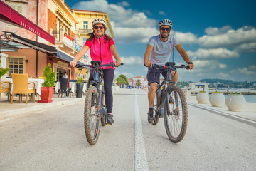 Active couple riding an E-Bike during vacations in the south