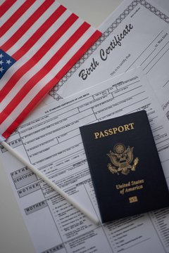 U.S. standard certificate of live birth application form next to American flag, Passport of USA and Birth Certificate template. USA Birthright citizenship concept. Vertical perspective.