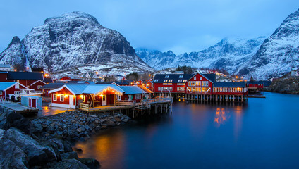 Panoramic overview of the small fishing village of A (Moskenes) at the end of the road of the Lofoten islands archipelago in northern Norway - Red rorbuer on stilts in winter at dawn