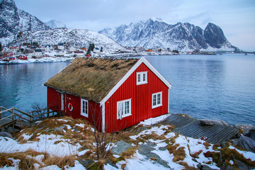 Red rorbu along the coast of Reine in the Lofoten Islands archipelago, Northern Norway in winter - View over the fjord from a traditionnal fishing hut during the polar night in the Arctic