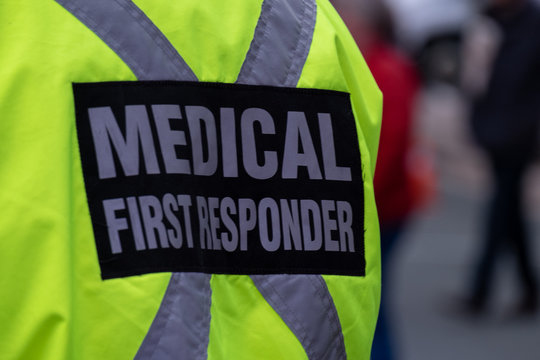 Medical First Responder wearing a bright yellow jacket with a reflective material in across on the person's back.  Medical first responder wearing a bright yellow coat with a grey reflective cross.