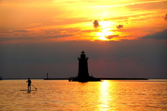 Silhouette of a light house and a man on a paddle board during sunset at Cape Henlopen State Park, Lewes, Delaware, U.S.A