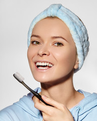 Beautiful Woman in Headband with Great Teeth holding Tooth Brush. Daily Routine Teethcare Treatment for Happy Smile