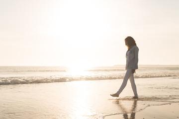 Fototapeta Full Length Of Woman Walking At Beach Against Sky During Sunset