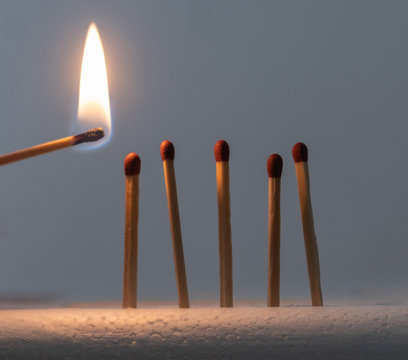 Close-Up Of Burning Matchstick Against Gray Background