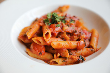 Penne arrabiata pasta tomato sauce with spices italian food on wood background