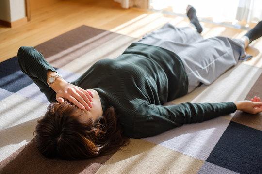 リビングで横になる女性 休憩 疲労 疲れ