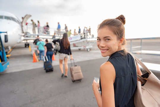 Travel woman boarding airplane at airport. Happy young Asian lady tourist walking on outside tarmac leaving for vacation trip with carry-on luggage suitcase.