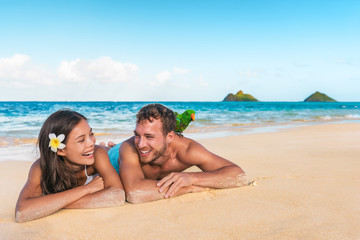 Beach people Hawaii honeymoon young couple laughing tourists with bird pet on shoulder - tourist...