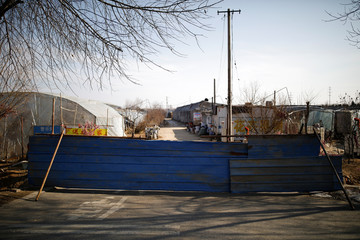 A barrier of metal sheets blocking a road to prevent outsiders from entering is seen at a community, as the country is hit by an outbreak of the new coronavirus, on the outskirts of Beijing