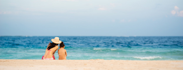 砂浜に座るビキニを着た母と娘