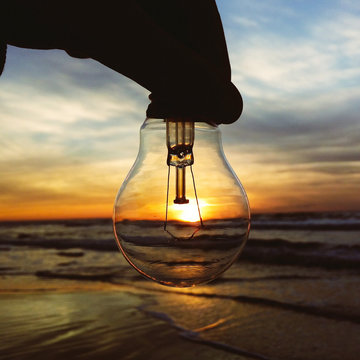 Cropped Silhouette Hand Of Person Holding Light Bulb At Beach Against Sky During Sunset