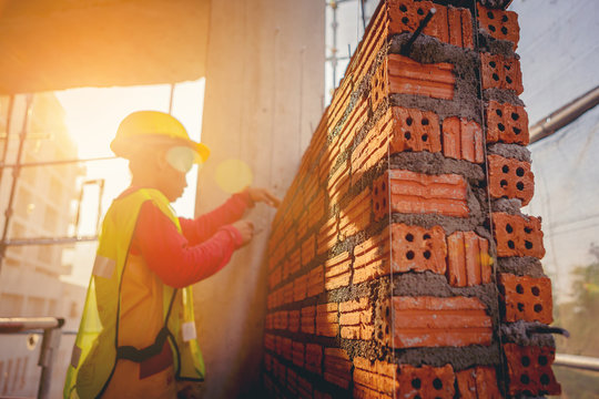 Bricklayer construction worker installing red brick masonry on exterior wall at outdoors construction site
