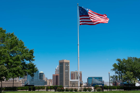 American Flag In City Against Clear Blue Sky