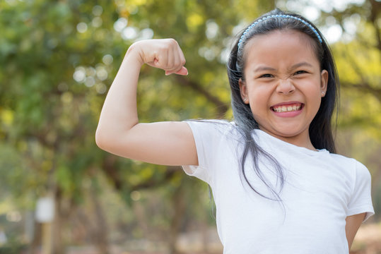 happy Little asian girl child standing showing front teeth with big smile.  showing arms muscles smiling proud. Looking camera showing biceps. fresh healthy green bio background. Fitness concept.