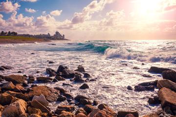 Fototapete - Rocky seashore at sunset. View of Bat Yam city from Tel Aviv - Jafo, Israel.