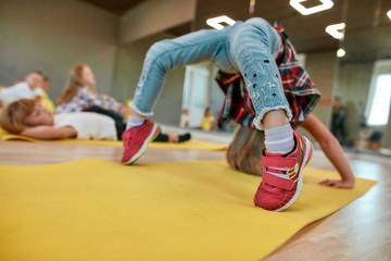 Staying flexible. Little girl making backbend on yoga mat in the dance studio. Group of children doing gymnastic exercises