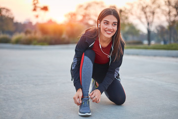 Young modern woman tying running shoes in urban park.