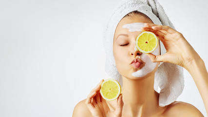 Foto auf AluDibond Spa Cosmetology, skin care, face treatment, spa and natural beauty concept. Woman with facial mask holds lemons.
