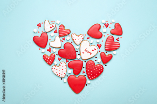 Valentine's Day heart made of coockies in shape of hearts on blue background. Flat lay, greeting card.