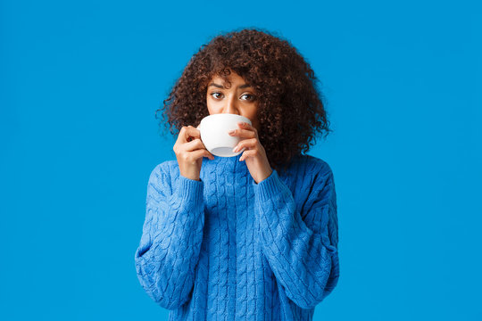 Girl listening to fresh gossips and sipping tea. Intrigued and relaxed good-looking african american woman having girlfriends meeting, drinking coffee from cup and looking camera interested