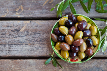 Ingelijste posters Olijfboom Assortment of fresh olives on a plate with olive tree brunches. Wooden background. Top view. Copy space.