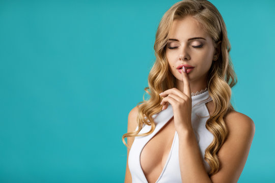 Portrait of beautiful sexy curly blonde woman in white dress asking to be quiet with finger on lips on blue background. copy space. woman showing shh sign