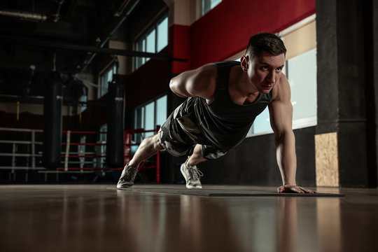 Man doing plank exercise in modern gym