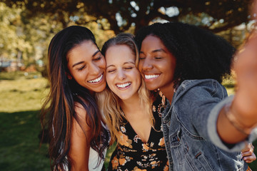 Close up portrait of smiling multiracial millennial women laugh stand posing for group picture together - Group of friends taking a selfie outdoors in the park on a sunny day