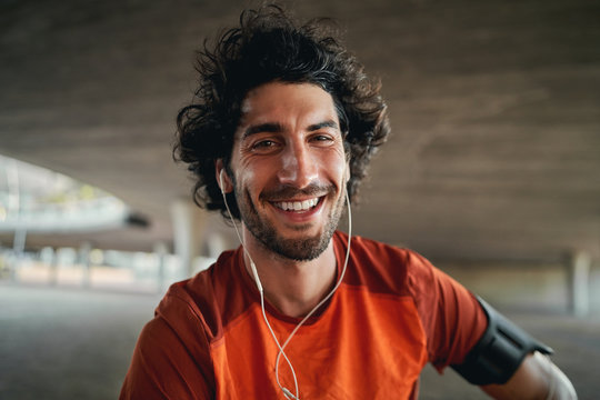 Portrait of happy young male runner with earphones in his ears looking at camera outdoor smiling - excited fit male