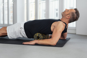 Man using a foam roller to massage his back