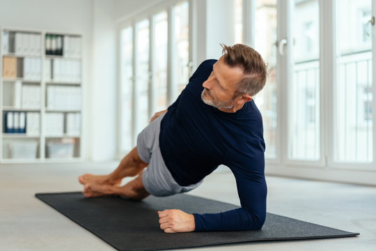 Middle-aged man working out doing side stretches