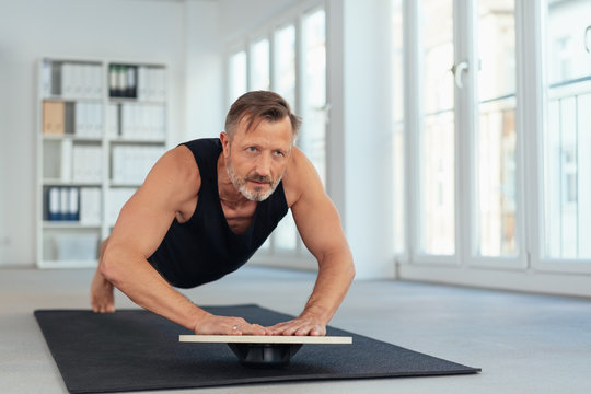 Middle-aged man exercising plank on balance board