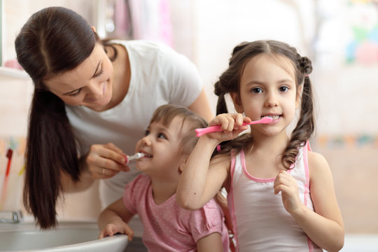 Happy family mom and her kids in bathroom. Mom teaches teeth brushing her younger daughter