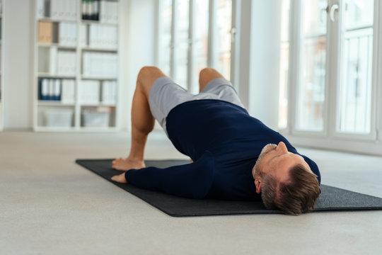 Man doing exercises, lying on back in office