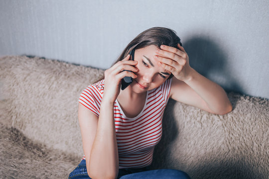 Young woman talking mobile phone at home, upset and holding her head. Having problem.