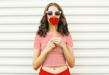 Portrait beautiful young woman with red heart shaped sunglasses blowing lips sending sweet air kiss...