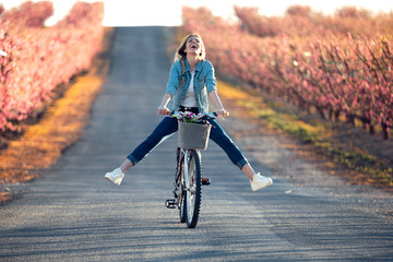 Pretty young woman with a vintage bike enjoying the time in cherry field in springtime. Fototapete
