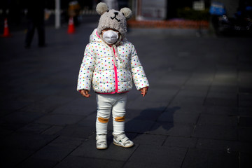 A little girl wearing a protective mask stands on a street in Shanghai