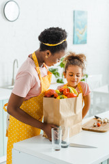 attractive african american mother and daughter looking at paper bag with groceries