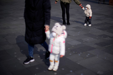 A little girl wearing a protective mask is pictured on a street in Shanghai