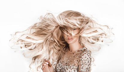 Tuinposter Kapsalon Blonde girl with long and shiny wavy hair . Beautiful model with curly hairstyle .