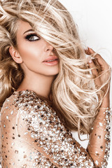 Blonde girl with long and shiny wavy hair . Beautiful model with curly hairstyle .