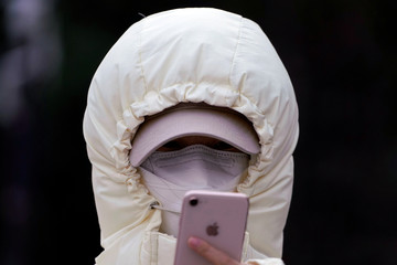 A woman wearing a mask checks her mobile phone in Shanghai