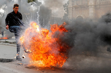 A Palestinian demonstrator kicks a burning tire during a protest against the U.S. president Donald Trump's Middle East peace plan, in Bethlehem in the Israeli-occupied West Bank