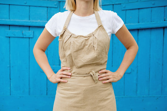 woman in apron standing on wooden vintage background. Entrepreneurship, craftsman, artisan, craft, service, cook, barista, small business, workplace concept. Mock up