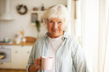 Positive friendy looking senior elderly woman with gray hair and wrinkles spending day at home,...